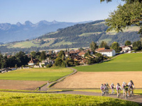 Switzerland-Day-3-Far-Scenic-Shot-Of-Pack-Cycling-Out-Of-Small-Village